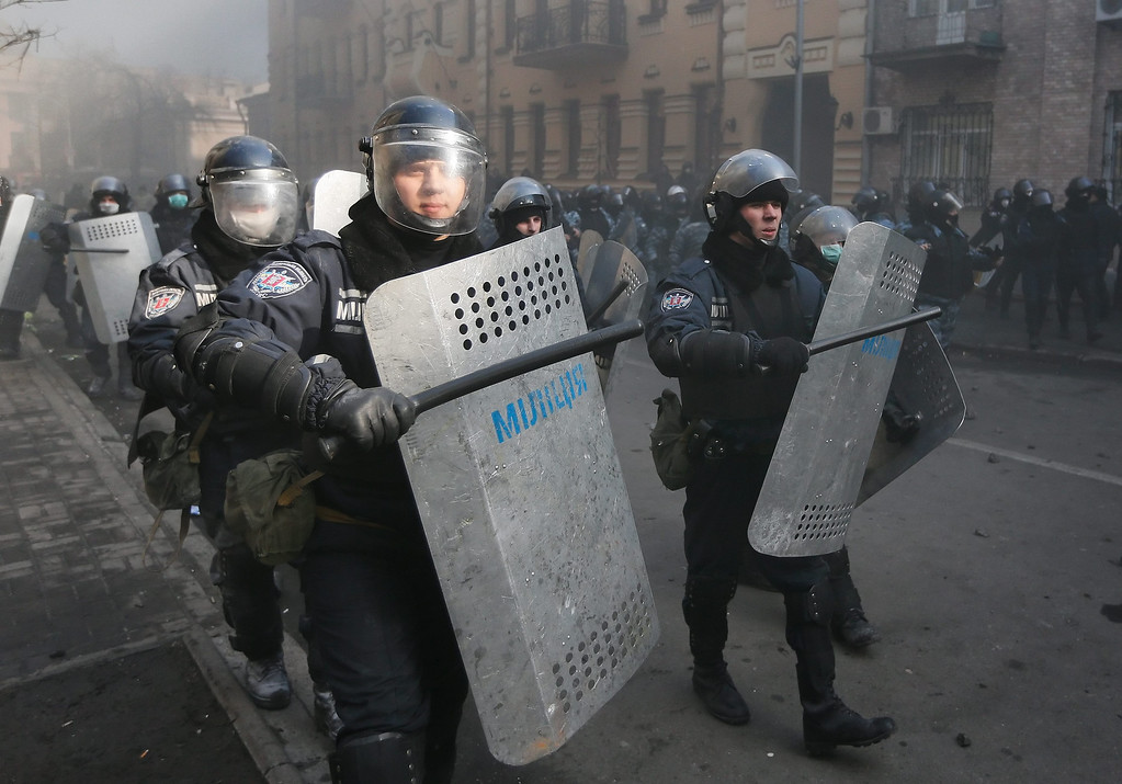 . Riot policemen hit their shields to make noise as they clash with protesters during the continuing protest in downtown Kiev, Ukraine, 18 February 2014.   EPA/SERGEY DOLZHENKO