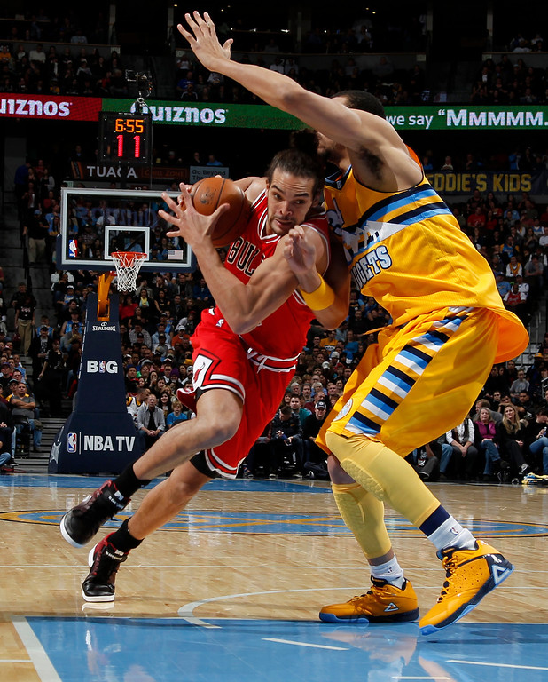 . Chicago Bulls center Joakim Noah, left, drives for a shot past Denver Nuggets forward JaVale McGee in the second quarter of an NBA basketball game in Denver on Thursday, Feb. 7, 2013. (AP Photo/David Zalubowski)