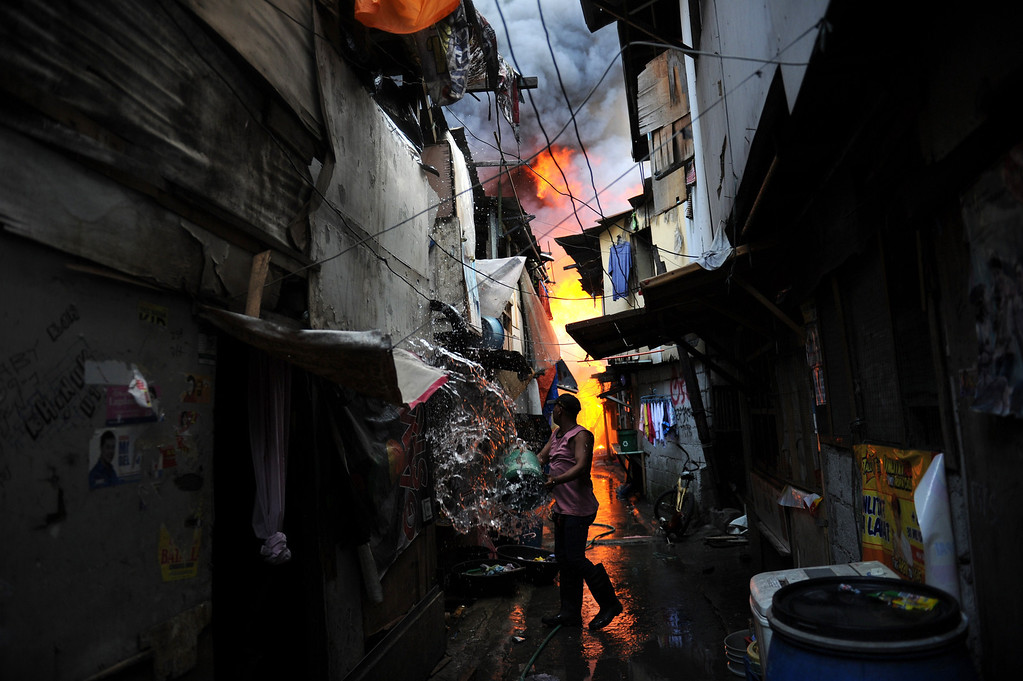. A resident tries to put out a fire after a blaze engulfed a shanty town at the financial district of Manila on July 11, 2013. There were no immediate reports of casualties from the blaze, which occurred mid-morning amid government plans to relocate thousands of families living in areas vulnerable to floods and typhoons. TED ALJIBE/AFP/Getty Images