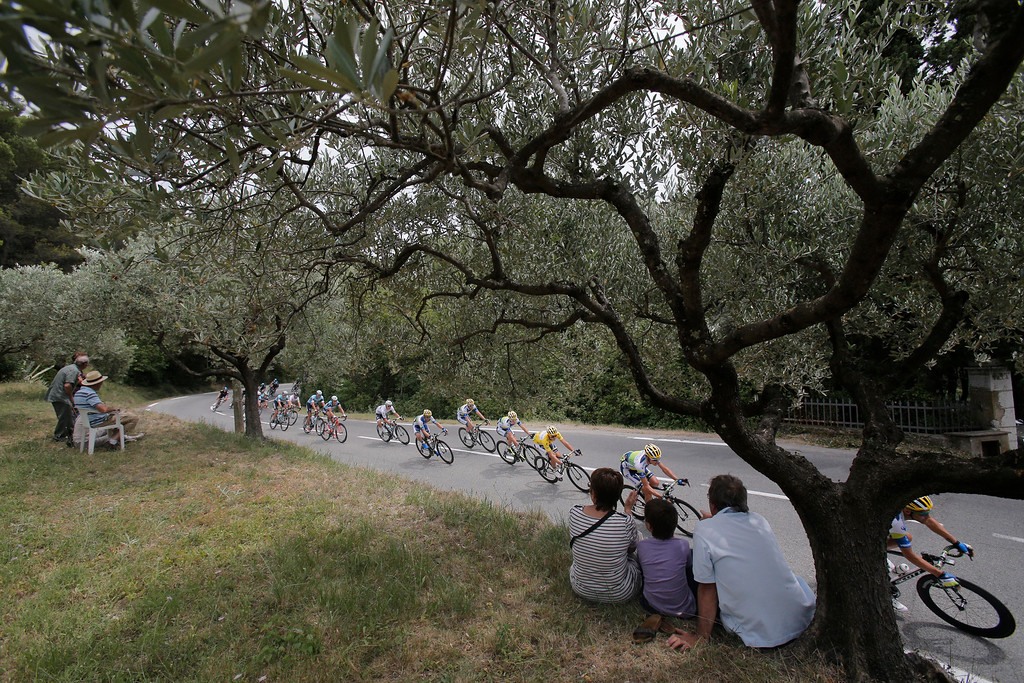 . Spectators sit under olive trees as the pack with Simon Gerrans of Australia, wearing the overall leader\'s yellow jersey, center, passes during the fifth stage of the Tour de France cycling race over 228.5 kilometers (142.8 miles) with start in Cagnes-sur-Mer and finish in Marseille, southern France, Wednesday July 3, 2013. (AP Photo/Christophe Ena)