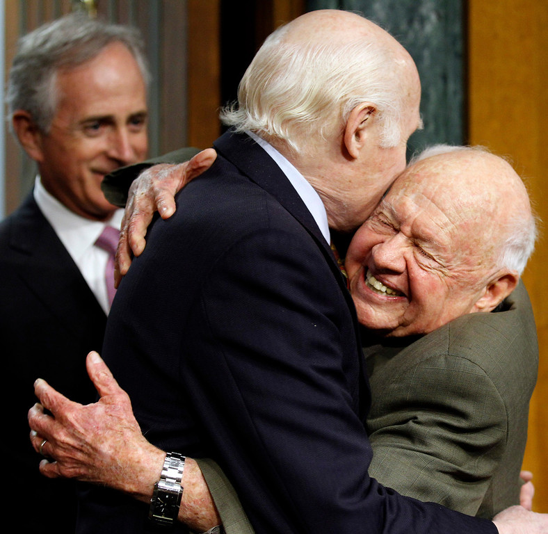 . In this Wednesday, March 2, 2011, file photo, Senate Aging Committee Chairman Sen. Herb Kohl. D-Wis., center, gets a hug from entertainer Mickey Rooney, right, on Capitol Hill in Washington, as Sen. Bob Corker, R-Tenn., looks on at left, prior to Rooney testifying about elder abuse, before the committee. (AP Photo/Alex Brandon, File)