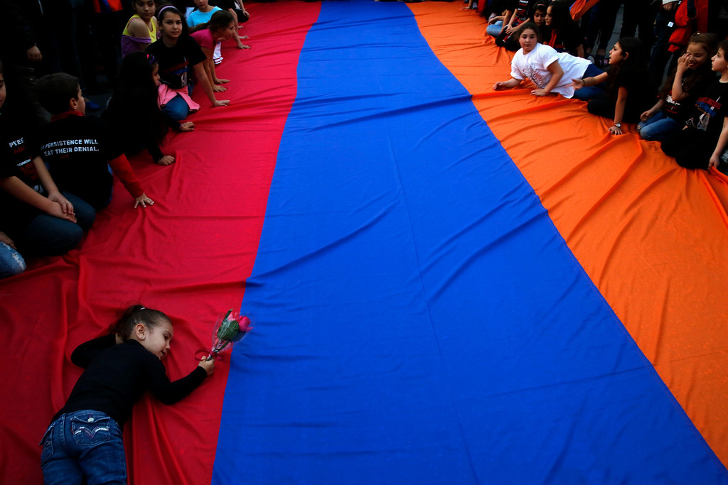 . An Armenian girl holds a rose as she lies on a huge Armenian flag during a demonstration near the Turkish embassy in central Athens, April 24, 2013. Hundreds of Armenians marched to commemorate the 98th anniversary of the mass killing of Armenians in the Ottoman Empire in 1915. Twenty one countries worldwide, including Greece, Russia, and France as well as the European parliament recognize the mass killings as an act of genocide, despite strong objections from Turkey. REUTERS/Yannis Behrakis