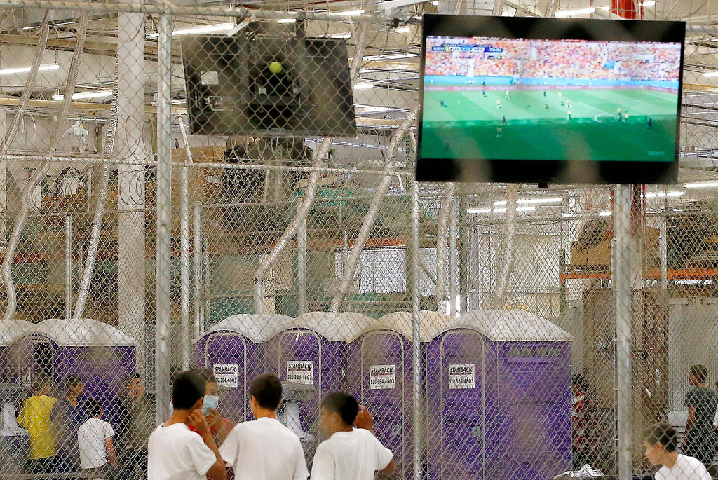 . Detainees watch a World Cup soccer match from a holding cell where hundreds of mostly Central American immigrant children are being processed and held at the U.S. Customs and Border Protection Nogales Placement Center on Wednesday, June 18, 2014, in Nogales, Ariz.   (AP Photo/Ross D. Franklin, Pool)