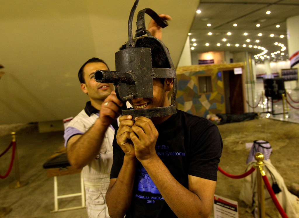 . An Iraqi man tries on a torture device used by the regime of Iraq\'s ousted leader Saddam Hussein at the Shaheed Monument in Baghdad, Iraq, Friday, May 24, 2013.  (AP Photo/Khalid Mohammed)