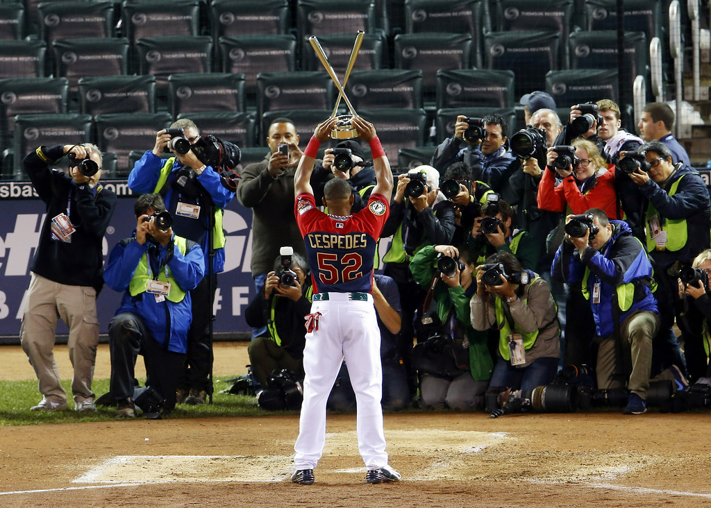 . American League\'s Yoenis Cespedes, of the Oakland Athletics, center, celebrates with the trophy after winning the MLB All-Star baseball Home Run Derby, Monday, July 14, 2014, in Minneapolis. Cespedes defeated National League\'s Todd Frazier, of the Cincinnati Reds, in the finals. (AP Photo/Paul Sancya)
