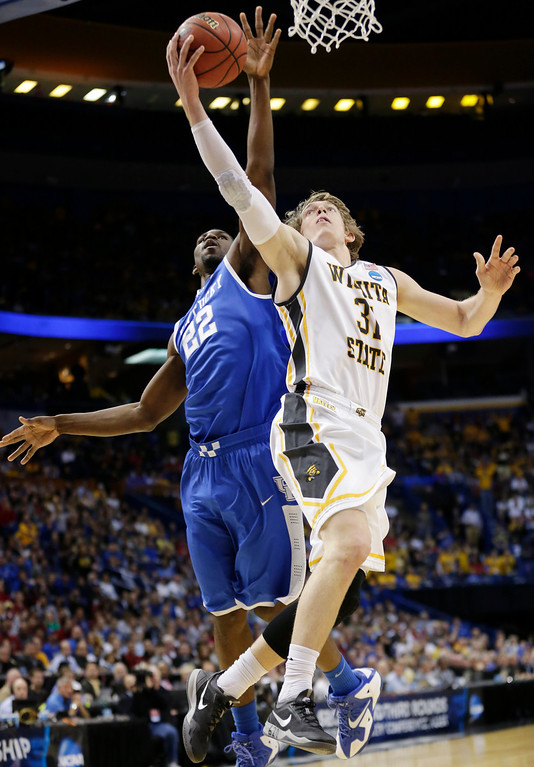 . Wichita State guard Ron Baker (31) shoots as Kentucky forward Alex Poythress (22) defends during the first half of a third-round game of the NCAA college basketball tournament Sunday, March 23, 2014, in St. Louis. (AP Photo/Charlie Riedel)
