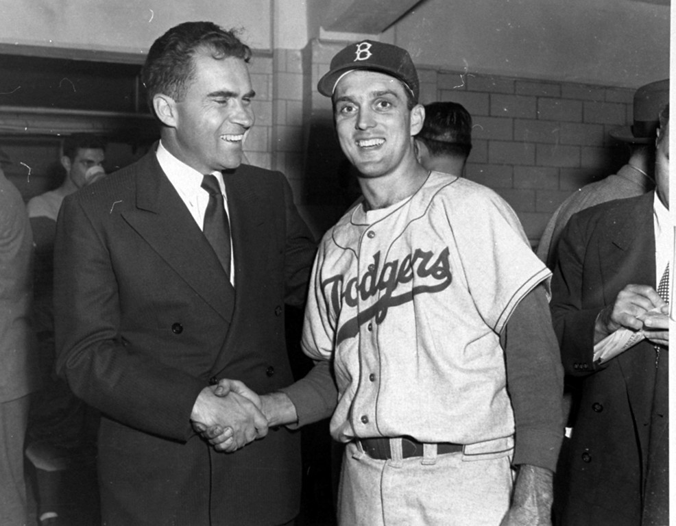 . Sen. Richard Nixon, GOP Vice Presidential candidate, has a smile and a handshake for Brooklyn Dodgers hurler Carl Erskine after his eleven-inning, 6-5 win over the Yankees in the fifth World Series game at Yankee Stadium in New York City, October 5, 1952.  Carl, loser in the second game of the series, October 2, gave the Yanks only five hits as the Dodgers took a 3-2 lead in games.  Sen. Nixon witnessed the game from a box seat behind the Brooklyn dugout.  (AP Photo)