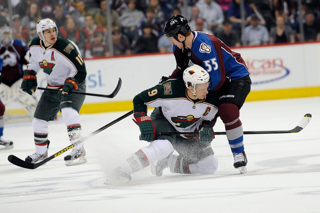. Mikko Koivu (9) of the Minnesota Wild drops to the ice as he dumps the puck off to a teammate while being checked by Cody McLeod (55) of the Colorado Avalanche during the first period, Saturday, April 27, 2012 at Pepsi Center. Seth A. McConnell, The Denver Post