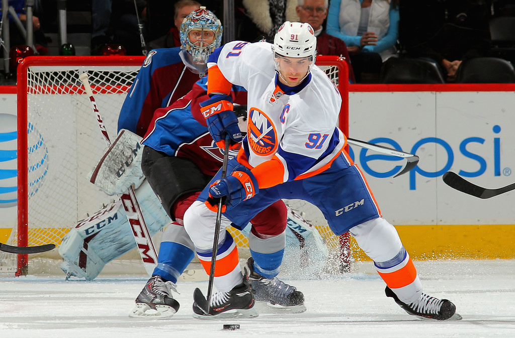 . DENVER, CO - JANUARY 10:  John Tavares #91 of the New York Islanders controls the puck as goalie Semyon Varlamov #1 of the Colorado Avalanche defends the goal at Pepsi Center on January 10, 2014 in Denver, Colorado.  (Photo by Doug Pensinger/Getty Images)