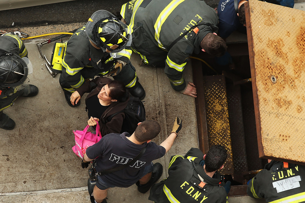 . New York City firefighters use an emergency staircase to evacuate passengers from a derailed F train on May 2, 2014 in the Woodside neighborhood of the Queens borough of New York City. According to the Metropolitan Transportation Authority  (MTA) the express F train was bound for Manhattan and Brooklyn when it derailed at 10:40 a.m. about 1,200 feet from the 65th station in Woodside, Queens with hundreds of passengers on board.  (Photo by Spencer Platt/Getty Images)
