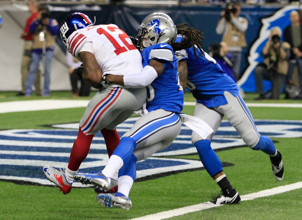 . New York Giants wide receiver Jerrel Jernigan (12) scores a touchdown defended by Detroit Lions cornerback Bill Bentley, center, and free safety Louis Delmas during the second quarter of an NFL football game, Sunday, Dec. 22, 2013, in Detroit. (AP Photo/Duane Burleson)