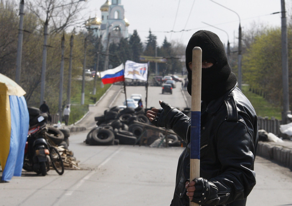 . A pro-Russian militiaman gestures and holds a stick as he guards a barricade bearing the Russian flag on the road leading to the eastern Ukrainian city of Slavyansk on April 14, 2014.   AFP PHOTO / ANATOLIY STEPANOV/AFP/Getty Images