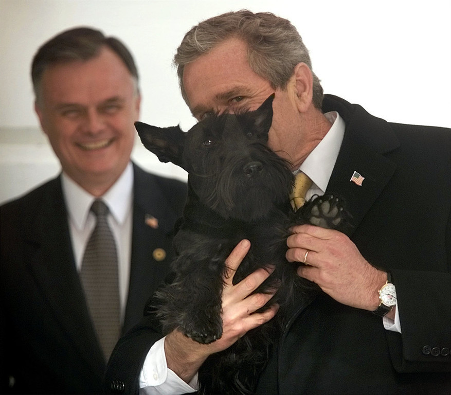 """. President Bush holds up his dog, Barney, and waves his paw to members of the media during his arrival at the South Lawn of the White House in this Wednesday, Feb. 27, 2002 file photo in Washington. In the back Gary Walters, chief usher at the White House. The chief usher of the Executive Mansion, Walters is retiring after more than 30 years _ and taking with him an intimate knowledge of everyday life at 1600 Pennsylvania Ave. \""""We have known Gary for many years and are especially grateful for making our family feel at home,\"""" President Bush and first lady Laura Bush said in a statement Tuesday, Oct. 24, 2006.  (AP Photo/Pablo Martinez Monsivais, File)"""