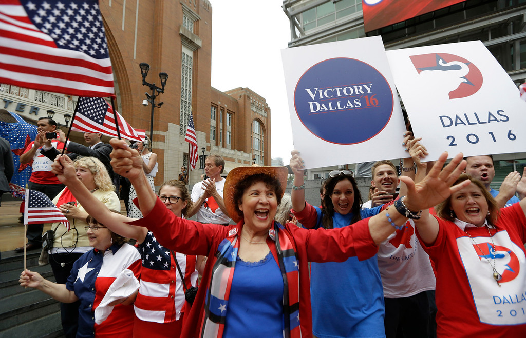 . Republican supporters cheer outside the American Airlines Center during a visit by members of the Republican National Committee scouting a 2016 Convention host site in Dallas, Thursday, June 12, 2014. American Airlines Center would serve as the convention site if Dallas\' bid is successful. Dallas is competing with Denver, Cleveland and Kansas City. (AP Photo/LM Otero)
