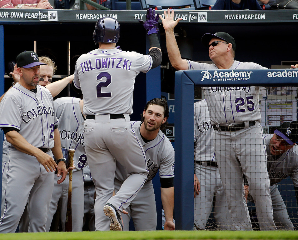 . Colorado Rockies\' Troy Tulowitzki, left, is high-fived by teammates after hitting a home run in the sixth inning of a baseball game against the Atlanta Braves, Saturday, May 24, 2014, in Atlanta. (AP Photo/David Goldman)