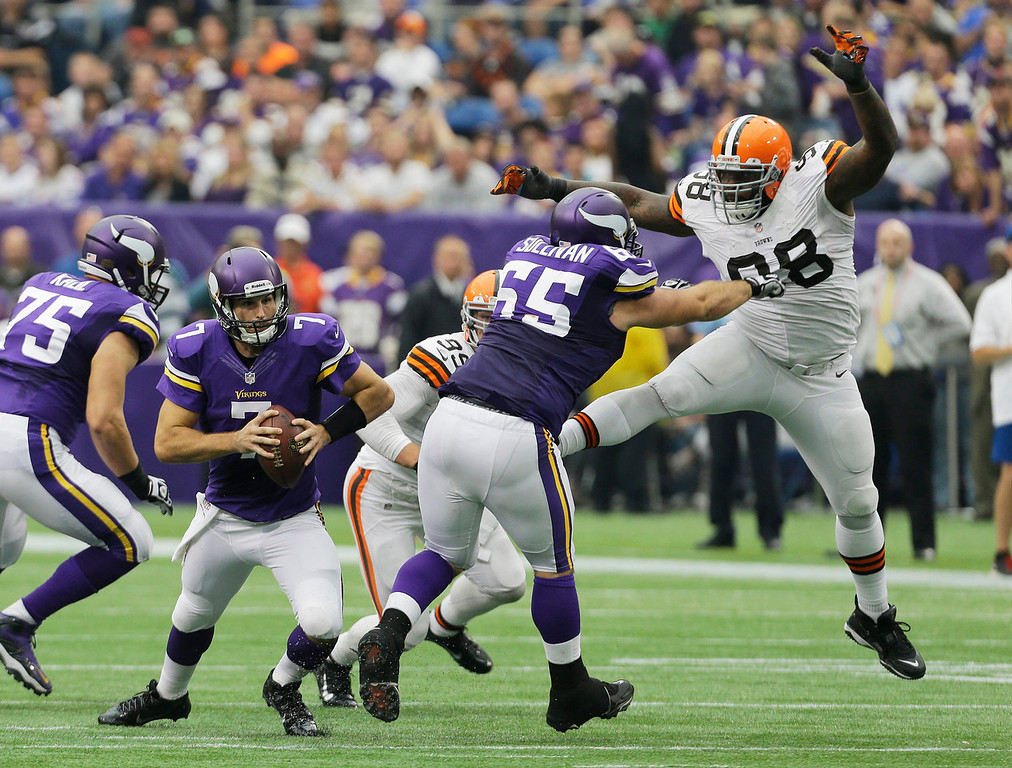 . Minnesota Vikings quarterback Christian Ponder, left, runs to avoid the rush by Cleveland Browns nose tackle Phillip Taylor, right, as he is blocked by Minnesota Vikings center John Sullivan (65) during the first half of an NFL football game Sunday, Sept. 22, 2013, in Minneapolis. (AP Photo/Ann Heisenfelt)