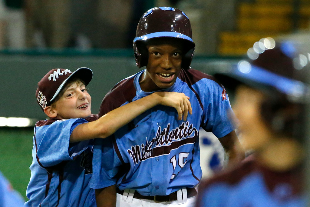 . Philadelphia\'s Kai Cummings, right, celebrates with teammate Erik Lipson, left, after hitting a solo home run off Chicago\'s Cameron Bufford during the fifth inning of an elimination baseball game at the Little League World Series tournament in South Williamsport, Pa., Thursday, Aug. 21, 2014. Chicago won 6-5. (AP Photo/Gene J. Puskar)