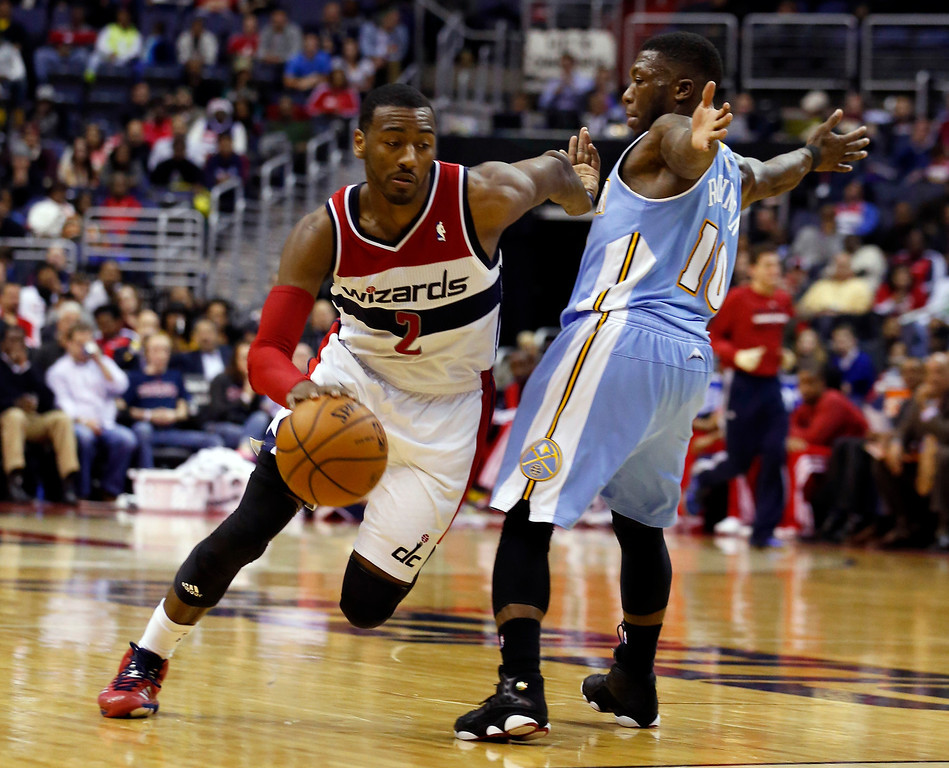 . Washington Wizards guard John Wall (2) gets past Denver Nuggets guard Nate Robinson (10) in the first half of an NBA basketball game on Monday, Dec. 9, 2013, in Washington. The Nuggets won 75-74. (AP Photo/Alex Brandon)