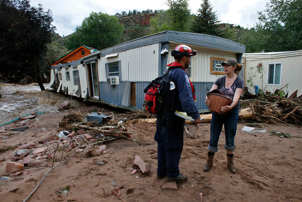 . Local resident Holly Rob talks with an emergency responder as she recovers belongings from her home which was nearly swept away in flooding, in Lyons, Colo., Friday Sept. 13, 2013. (AP Photo/Brennan Linsley)