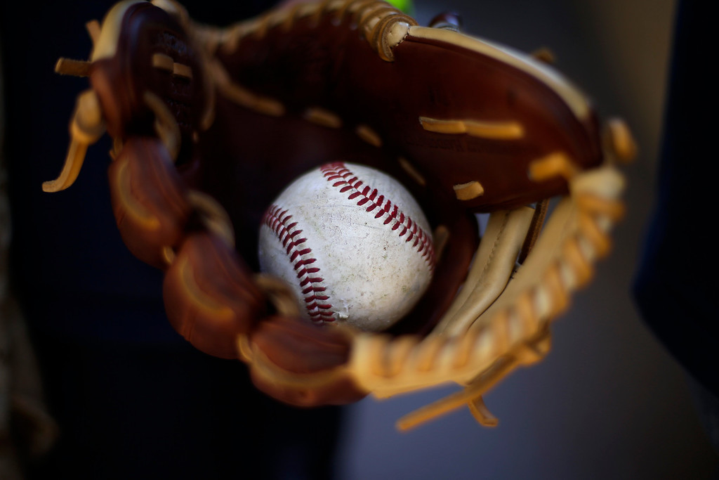 . Peyton Berroth carries a baseball in his glove as he arrives to Petco Stadium before an opening day baseball game between the Los Angeles Dodgers and the San Diego Padres on Sunday, March 30, 2014, in San Diego. (AP Photo/Gregory Bull)