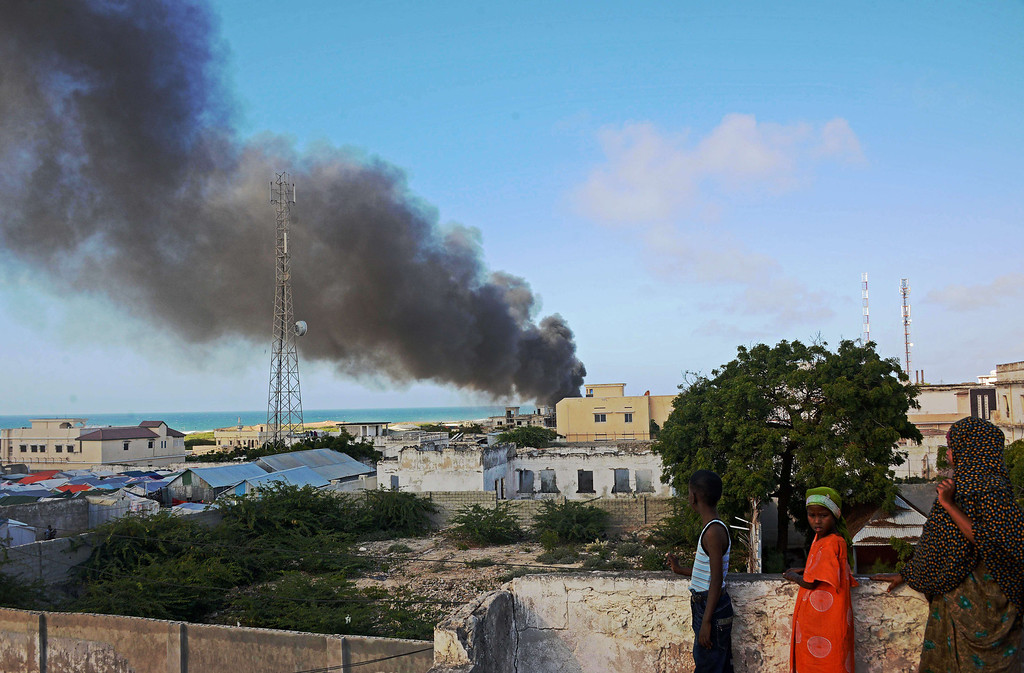. People look at smoke rising in the sky after the crash of an Ethiopian military cargo which landed and burst into flames at Mogadishu airport on August 9, 2013. AFP PHOTO/MOHAMED  Abdiwahab/AFP/Getty Images