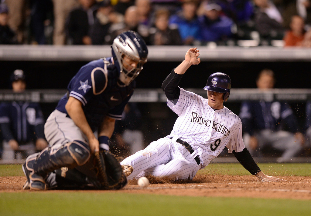 . DENVER, CO - MAY 15: Colorado baserunner DJ LeMahieu slid safely across the plate on a single by Charlie Blackmon in the seventh inning. The throw to San Diego catcher Nick Hundley was offline. The Colorado Rockies hosted the San Diego Padres at Coors Field  Friday night, May 16, 2014. (Photo by Karl Gehring/The Denver Post)