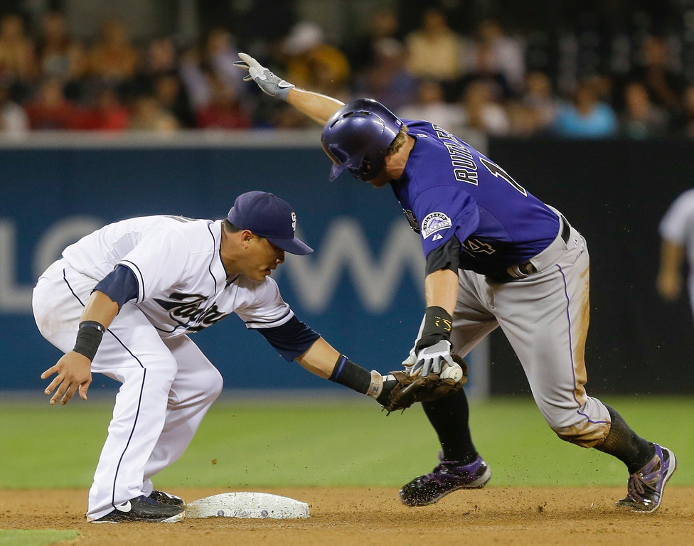 . Colorado Rockies\' Josh Rutledge,right, hand rest on the glove of San Diego Padres shortstop Everth Cabrera, left, but Rutledge  is called safe after stealing second base in the fifth inning of a baseball game in San Diego, Tuesday, July 9, 2013. (AP Photo/Lenny Ignelzi)