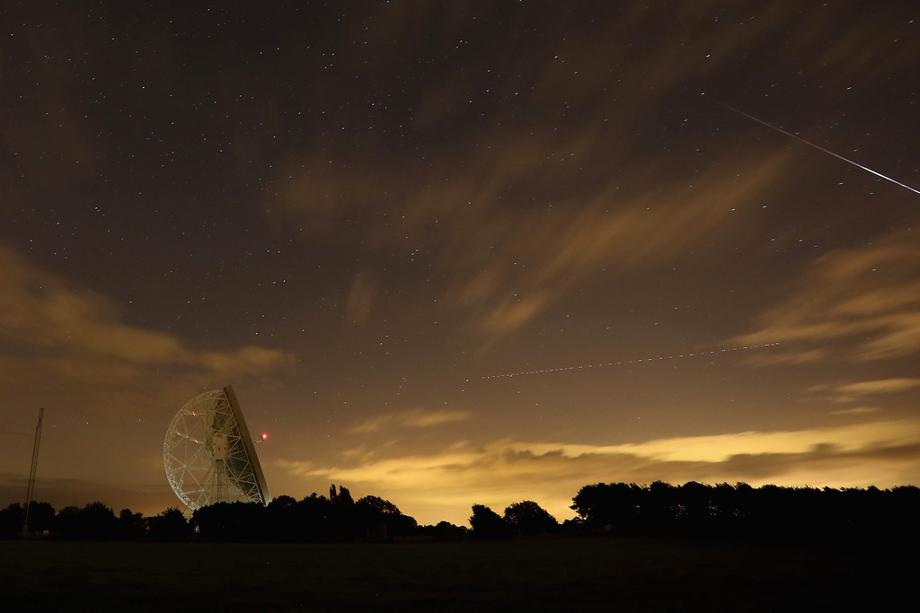 . HOLMES CHAPEL, UNITED KINGDOM - AUGUST 13:  A Perseid meteor (R) streaks across the sky past the light trail of an aircraft over the Lovell Radio Telescope at Jodrell Bank on August 13, 2013 in Holmes Chapel, United Kingdom.The annual display, known as the Perseid shower because the meteors appear to radiate from the constellation Perseus in the northeastern sky, is a result of Earth\'s orbit passing through debris from the comet Swift-Tuttle.  (Photo by Christopher Furlong/Getty Images)