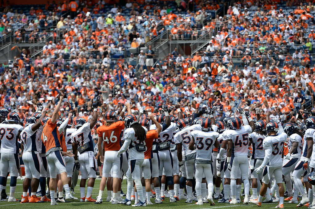 . The Denver Broncos meet at mid field as they prepare to head to drills on day four of the Denver Broncos 2014 training camp July 27, 2014 at Sports Authority Field at Mile High. (Photo by John Leyba/The Denver Post)