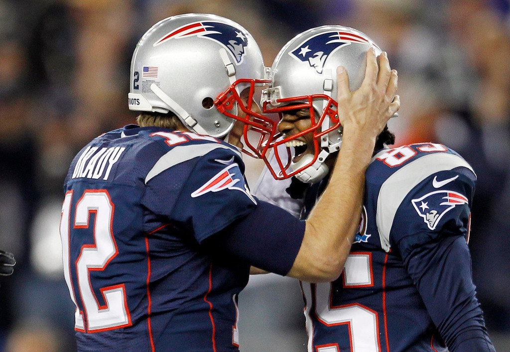 . New England Patriots quarterback Tom Brady (L) and wide receiver Brandon Lloyd celebrate after Lloyd caught a touchdown pass from Brady against the Houston Texans during the first half of their NFL football game in Foxborough, Massachusetts December 10, 2012. REUTERS/Jessica Rinaldi