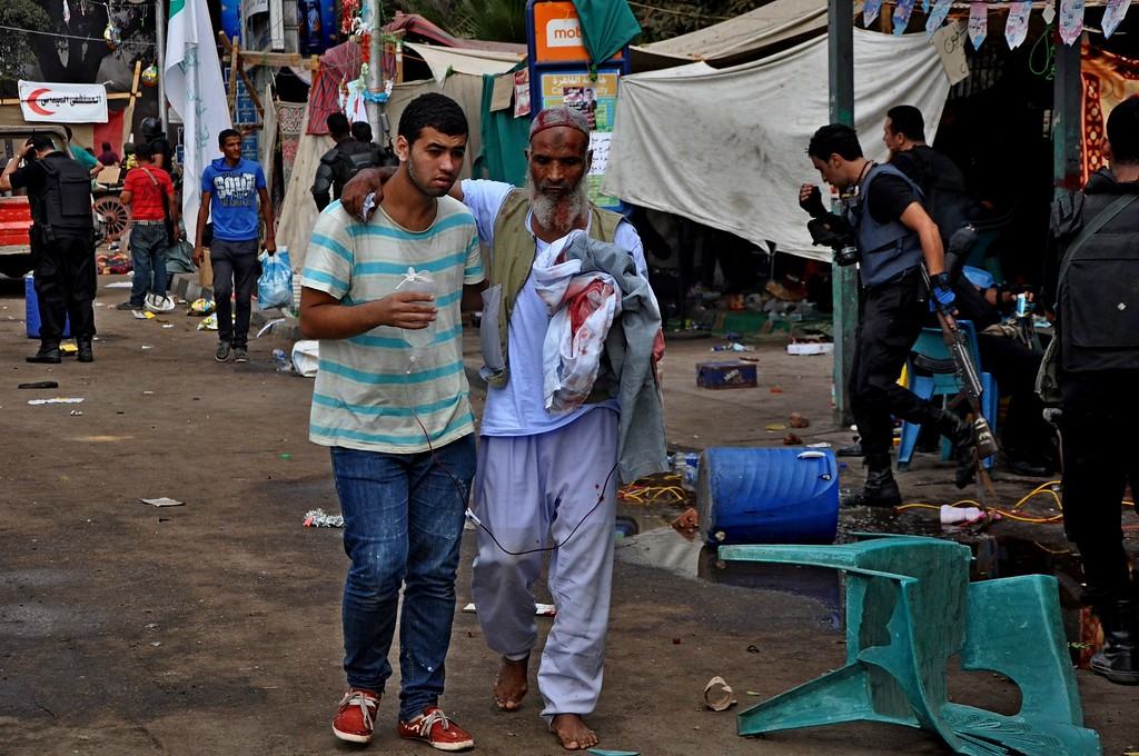 . A supporter of ousted Islamist President Mohammed Morsi helps another walk as Egyptian security forces clear a sit-in camp set up by  near Cairo University in Cairo\'s Giza district, Egypt, Wednesday, Aug. 14, 2013.  (AP Photo/Hussein Tallal)