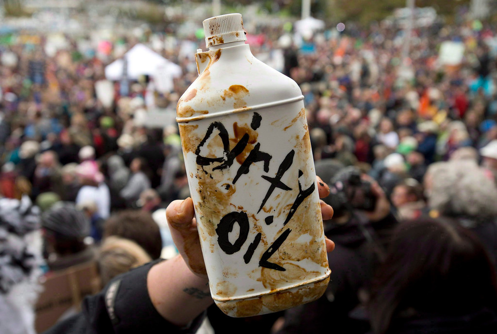 . A demonstrator holds up a prop representing dirty oil during a mass sit-in in front of the British Columbia legislature in Victoria, B.C. on, Oct. 22, 2012.    (AP Photo/The Canadian Press, Jonathan Hayward)