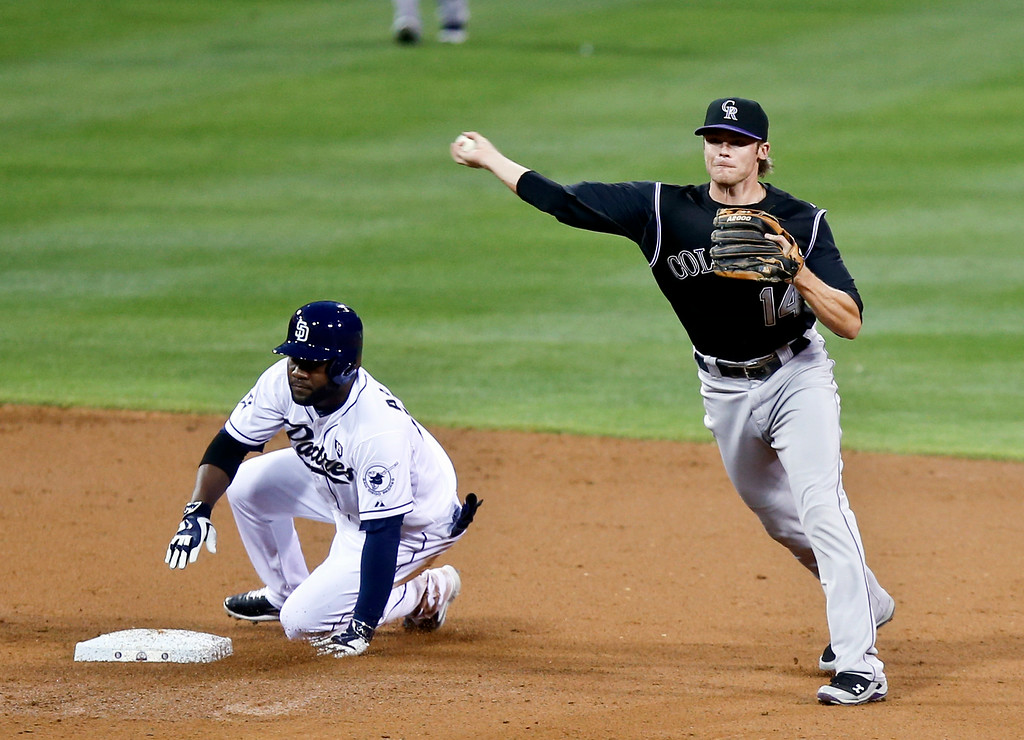 . Colorado Rockies shortstop Josh Rutledge, right, throws to first after getting the force out at second on San Diego Padres\' Abraham Almonte in the second inning of a baseball game Tuesday, Aug. 12, 2014, in San Diego. Rutledge\'s throw was late and the Padres\' runner scored from third on the play. (AP Photo/Lenny Ignelzi)