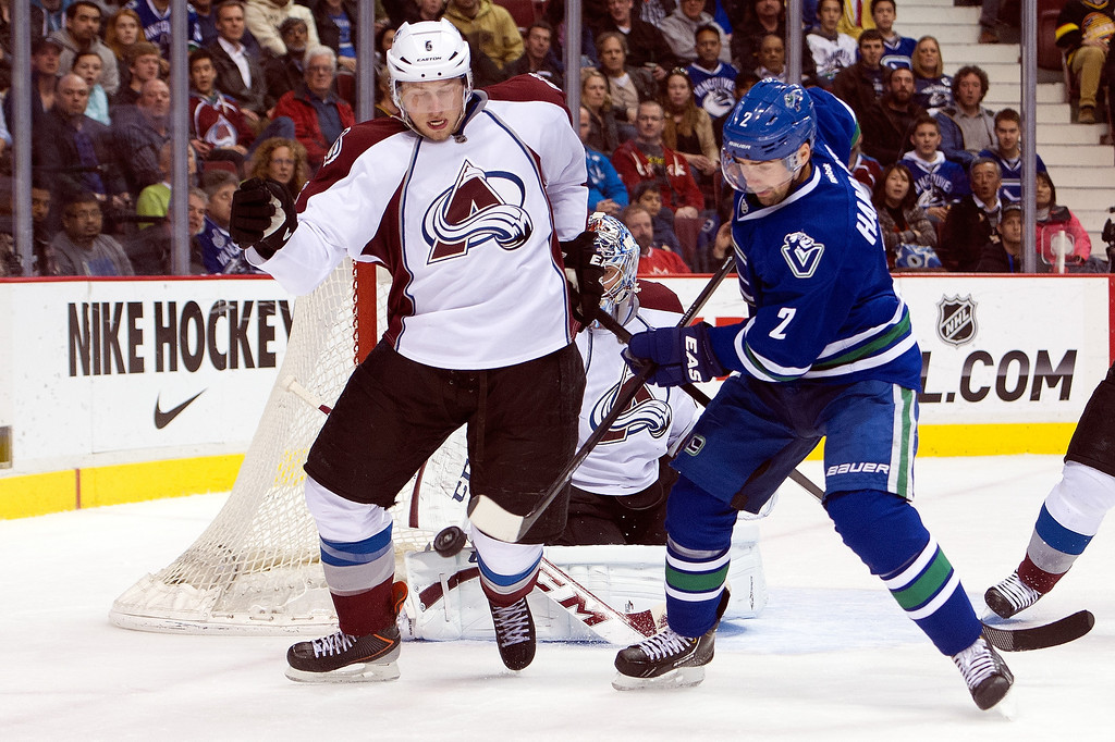 . Erik Johnson #6 of the Colorado Avalanche and Dan Hamhuis #2 of the Vancouver Canucks battle for the puck at the side of the net during the second period in NHL action on April 10, 2014 at Rogers Arena in Vancouver, British Columbia, Canada.  (Photo by Rich Lam/Getty Images)