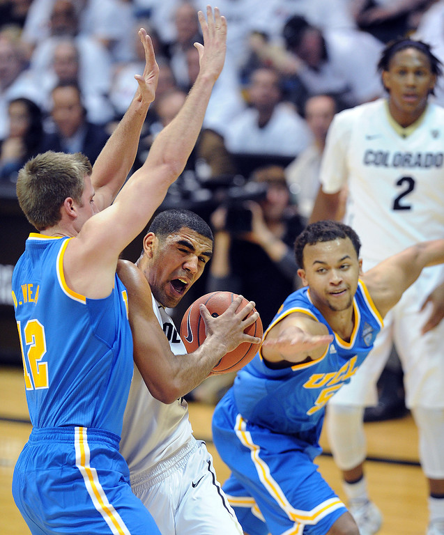 . Josh Scott of CU tries to get past David Wear, left, and Kyle Anderson of UCLA during the second half of the January 16, 2014 game in Boulder.  (Cliff Grassmick/Daily Camera)