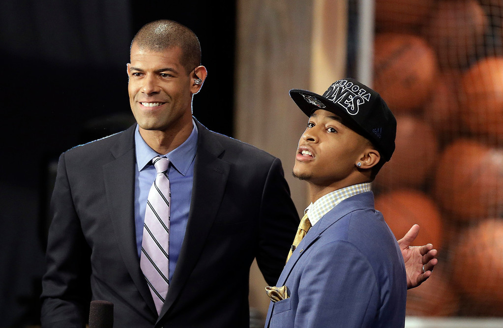 . Michigan\'s Trey Burke, right, is interviewed by Miami Heat\'s Shane Battier after being selected by the Minnesota Timberwolves in the first round of the NBA basketball draft, Thursday, June 27, 2013, in New York. (AP Photo/Kathy Willens)