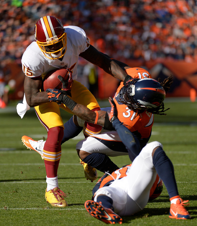 . DENVER, CO - OCTOBER 27: Washington Redskins wide receiver Josh Morgan (15) shakes off a tackle by Denver Broncos cornerback Omar Bolden (31) in the second quarter. The Denver Broncos take on the Washington Redskins at Sports Authority Field at Mile High in Denver on October 27, 2013. (Photo by Joe Amon/The Denver Post)
