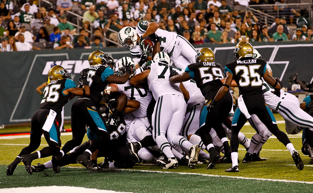 . EAST RUTHERFORD, NJ - AUGUST 17:   Kahlil Bell #24 of the NEw York Jets jumps over the line Jacksonville Jaguars during their preseason game at MetLife Stadium on August 17, 2013 in East Rutherford, New Jersey.  (Photo by Jeff Zelevansky/Getty Images)