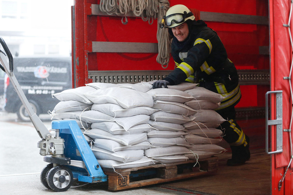 . A firefighter unloads sandbags from a fire engine in Westerland on the isle of Sylt, Germany, 05 December 2013. Storm front Xaver has reached the North Sea coast of Germany.  EPA/AXEL HEIMKEN