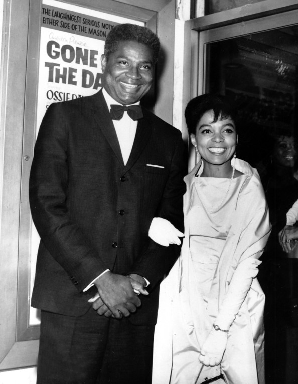 """. Ossie Davis, left, and Ruby Dee pose in front of their movie poster at the opening night gala of their film \""""Gone Are the Days!\"""" at the Trans-Lux East Theater on Sept. 23, 1963. The movie, starring the married couple, is based on Davis\'s play \""""Purlie Victorious.\"""" (AP Photo)"""
