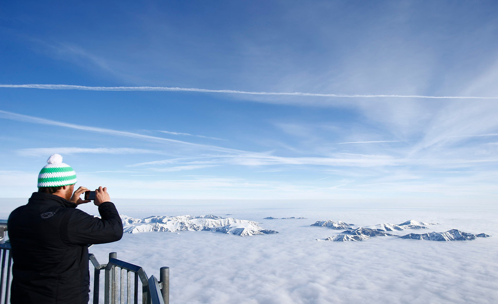 . A man takes a picture of fog covered mountain summits, from Germany\'s highest mountain the 2,962 metre (9,718 feet) Zugspitze, on a sunny Spring day in the Bavarian village of Grainau April 3, 2012. REUTERS/Dominic Ebenbichler (GERMANY - Tags: ENVIRONMENT CITYSPACE TPX IMAGES OF THE DAY)