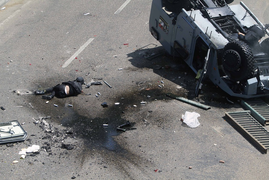 . A member of the security forces lies on the ground and another on his police vehicle that was pushed off the 6th of October bridge by protesters near the largest sit-in by supporters of ousted Islamist President Mohammed Morsi in the eastern Nasr City district of Cairo, Egypt, Wednesday, Aug. 14, 2013.  (AP Photo/Sabry Khaled)
