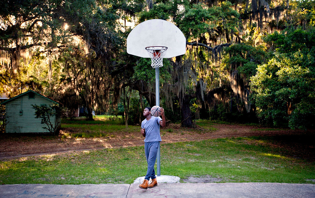 . Marvin Grovner, 16, plays with a basketball after returning home to the Hog Hammock community of Sapelo Island, Ga. from school on the mainland on Wednesday, May 15, 2013. (AP Photo/David Goldman)