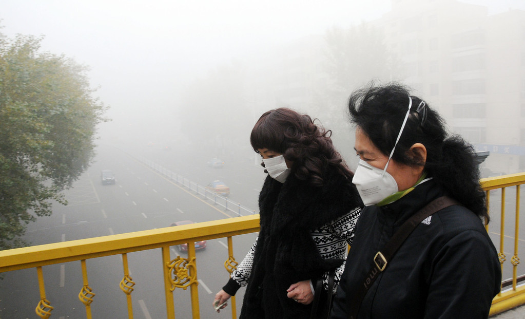 . Pedestrians wearing masks walk along a road as heavy smog engulfs the city on October 21, 2013 in Harbin, China. (Photo by ChinaFotoPress/Getty Images)