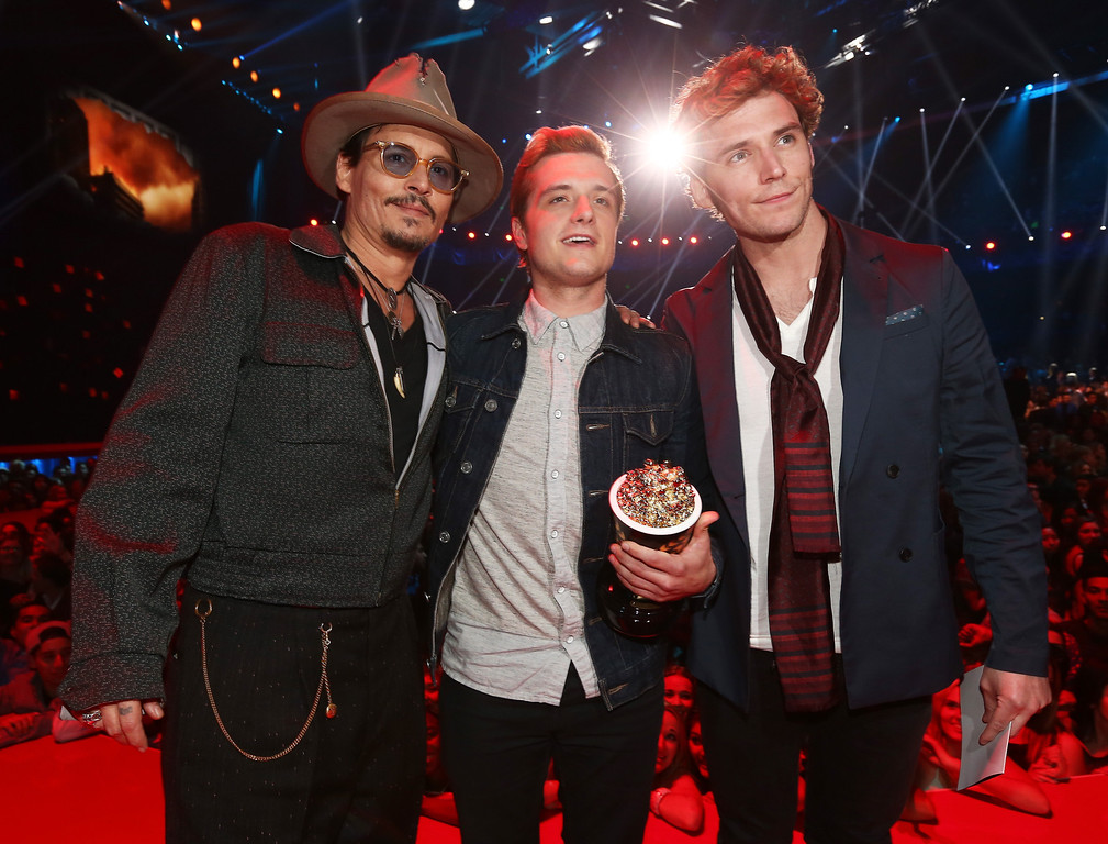 . (L-R) Actor Johnny Depp poses with actors Josh Hutcherson and Sam Claflin, winners of the Movie of the Year award for \'The Hunger Games: Catching Fire,\' at the 2014 MTV Movie Awards at Nokia Theatre L.A. Live on April 13, 2014 in Los Angeles, California.  (Photo by Christopher Polk/Getty Images)