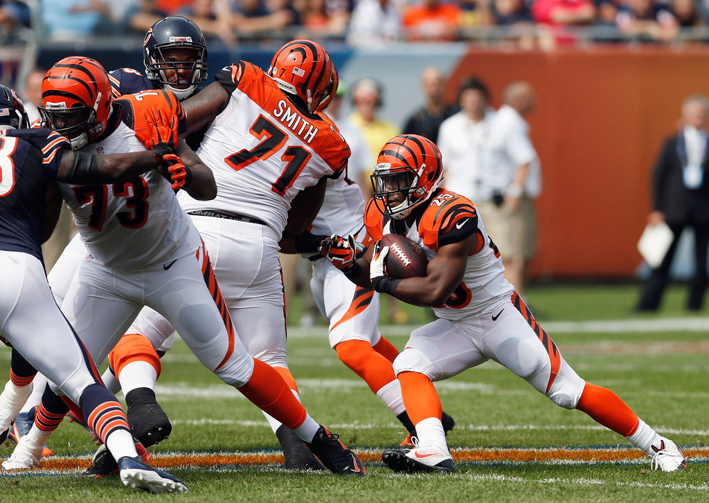 . Cincinnati Bengals running back Giovani Bernard (25) looks for running room against Chicago Bears defenders during the first half of an NFL football game, Sunday, Sept. 8, 2013, in Chicago. (AP Photo/Charles Rex Arbogast)