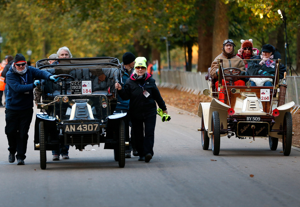. Participants, right, driving their 1905 De Dion Bouton car, drive past other participants pushing their 1903 De Dion Bouton car, that temporarily broke down, to the start line in London\'s Hyde Park, during the London to Brighton Veteran Car Run, Sunday, Nov. 3, 2013. Over 400 pre-1905 vehicles made their way on the historic 60-mile run from Hyde Park in London to coastal Brighton in southern England, in the world\'s longest running motoring celebration spanning 117 years. (AP Photo/Lefteris Pitarakis)