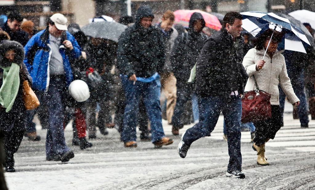 . Pedestrians cross an intersection at Penn Station during snowfall on Friday, March 8, 2013 in New York. (AP Photo/Bebeto Matthews)