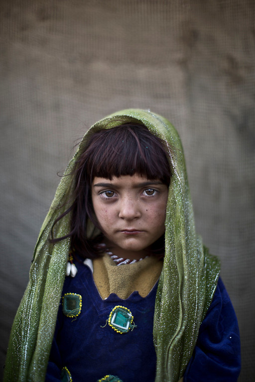 . In this Saturday, Jan. 25, 2014 photo, Afghan refugee girl, Zarlakhta Nawab, 6, poses for a picture, while playing with other children in a slum on the outskirts of Islamabad, Pakistan. For more than three decades, Pakistan has been home to one of the world�s largest refugee communities: hundreds of thousands of Afghans who have fled the repeated wars and fighting their country has undergone. Since the 2002 U.S.-led invasion of Afghanistan, some 3.8 million Afghans have returned to their home country, according to the U.N.�s refugee agency. (AP Photo/Muhammed Muheisen)