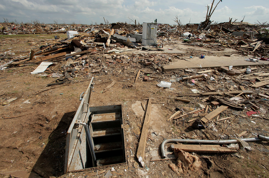 . In this May 26, 2013, file photo, an underground shelter is seen near tornado rubble in Moore, Okla.  (AP Photo/Charlie Riedel, File)